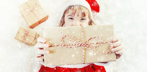 子供は白い背景にクリスマスの装飾と贈り物を持っています。選択フォーカス。
