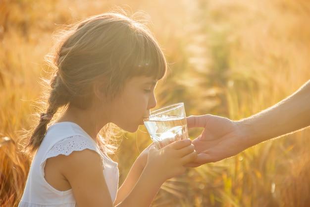 父親は子供にコップ一杯の水を与えます。セレクティブフォーカス