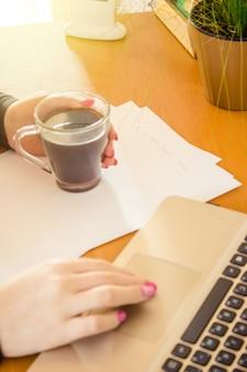 ノートパソコンは、キーボードと朝のホットコーヒーのカップのクローズアップ。セレクティブフォーカス