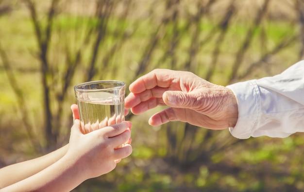 祖母は子供に一杯のきれいな水を与えます。セレクティブフォーカス