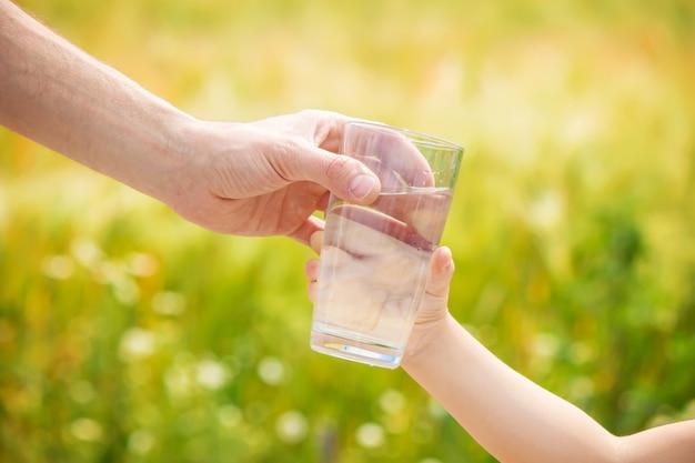 父親は子供にコップ一杯の水を与える。セレクティブフォーカス