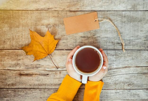 子供の手の中の紅茶と居心地の良い秋の背景。選択フォーカス。