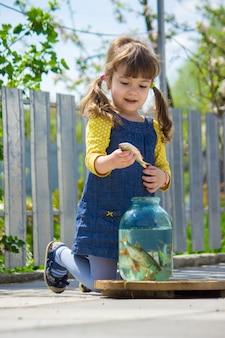 Ребенок ловит рыбу в банке