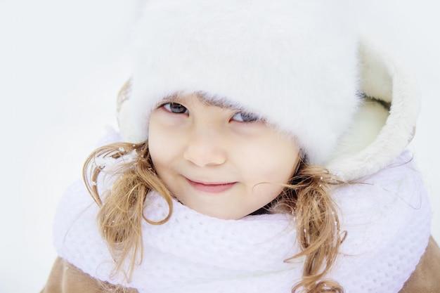 子供は冬に雪の中で遊ぶ。セレクティブフォーカス