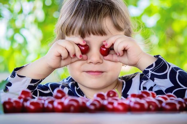 子供は庭でさくらんぼを摘んでいる。セレクティブフォーカス