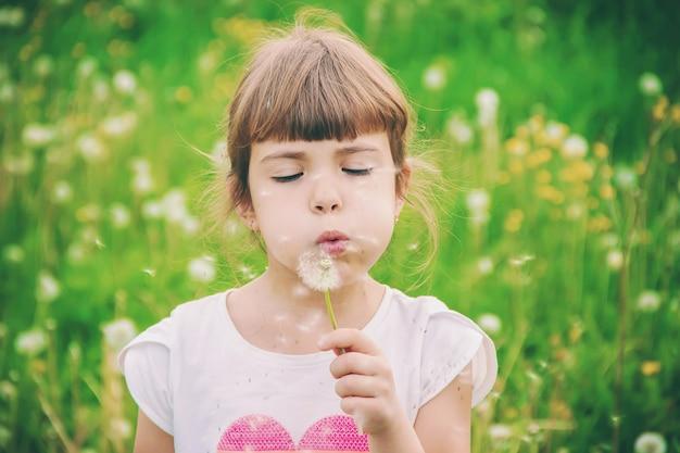 空気中のタンポポを吹く少女。セレクティブフォーカス