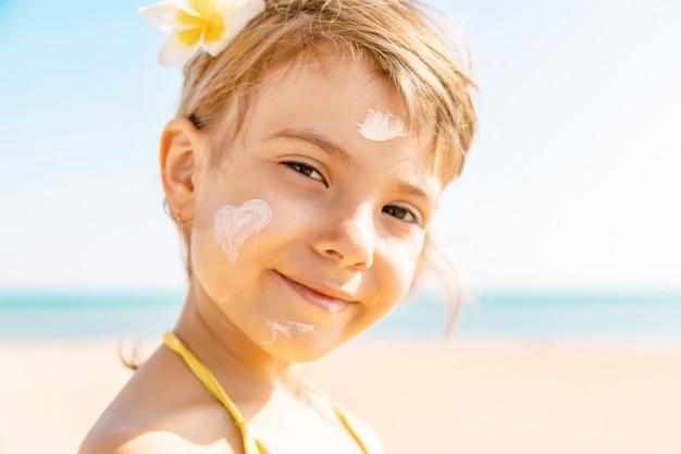 Ребенок на пляже мажет солнцезащитный крем. выборочный фокус.