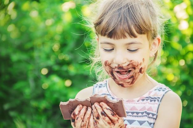 甘い歯の子供がチョコレートを食べる。セレクティブフォーカス