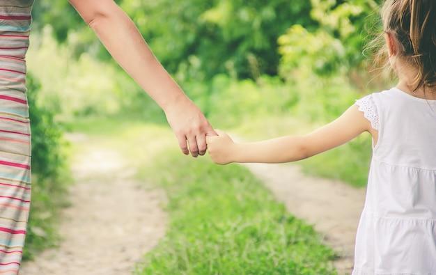 Мама и дочь идут по дороге, держась за руки.
