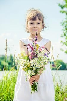 野生の花の花束を持つ子供。セレクティブフォーカス自然。