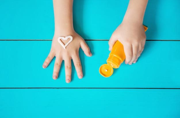 Солнцезащитный крем на руке ребенка. выборочный фокус.