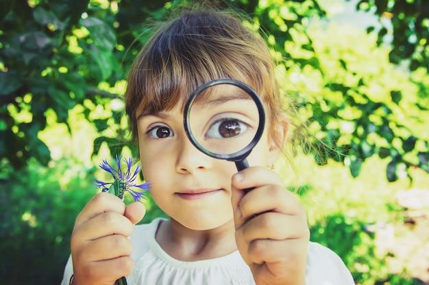 子供は虫眼鏡で探しています。増加する。セレクティブフォーカス