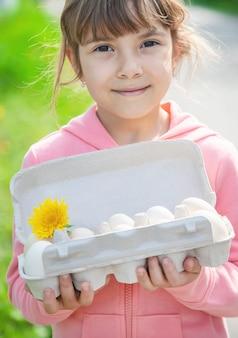 子供の手の中に自家製の卵。