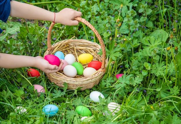 Крашенки домашние яйца в корзине и руках ребенка.