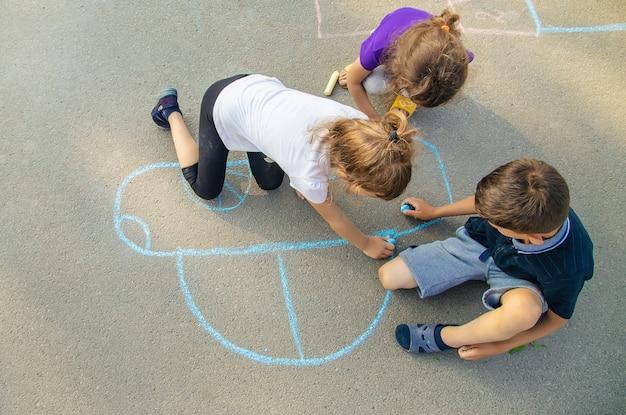 子供たちは歩道にチョークで車を描きます。セレクティブフォーカス