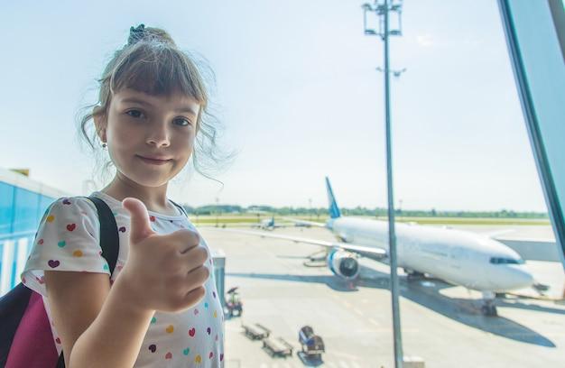 Ребенок в аэропорту на фоне самолета