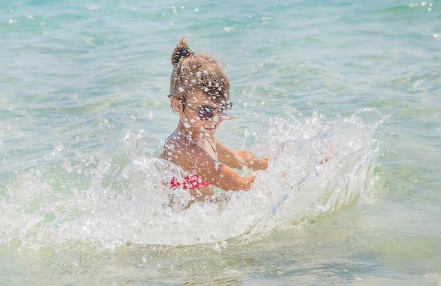 子供は海にスプレーをします