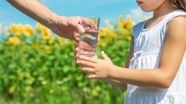 父親は畑の背景で子供に水を与えます