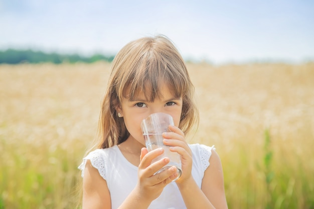 Ребенок пьет воду на фоне поля
