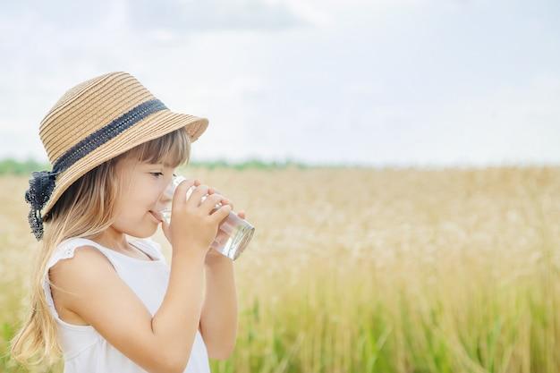 子供がフィールドの背景に水を飲む