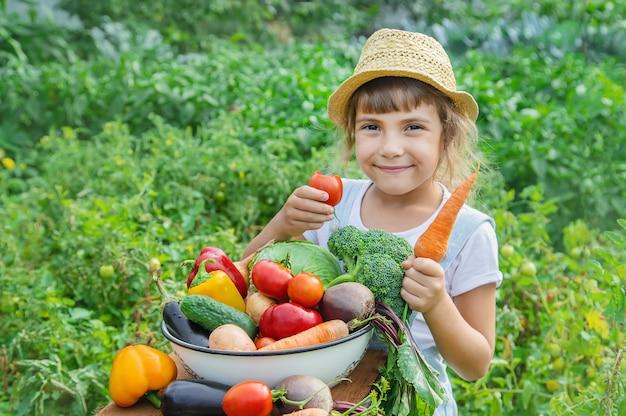 Ребенок в саду с овощами в руках.