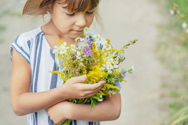 子供の手で野生の花を保持している女の子