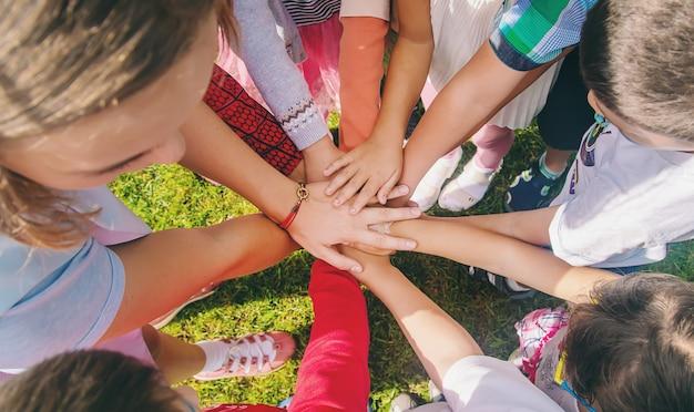 Дети сложили руки вместе, играют на улице