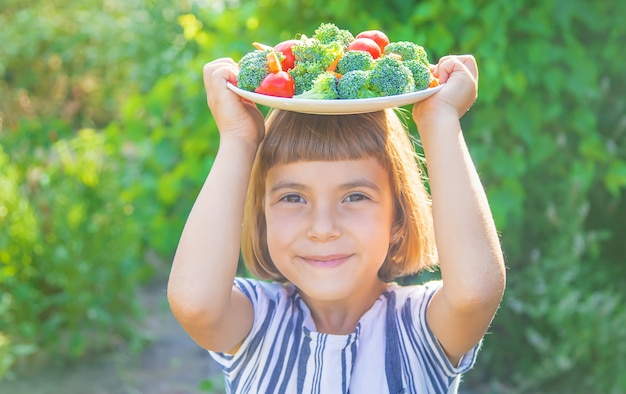 Ребенок ест овощи брокколи и морковь