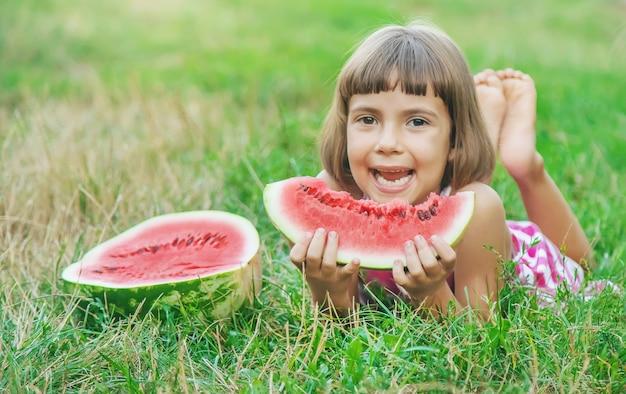 子供が庭でスイカを食べる