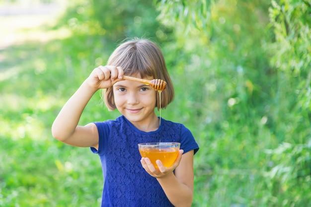 子供の手に蜂蜜のプレート