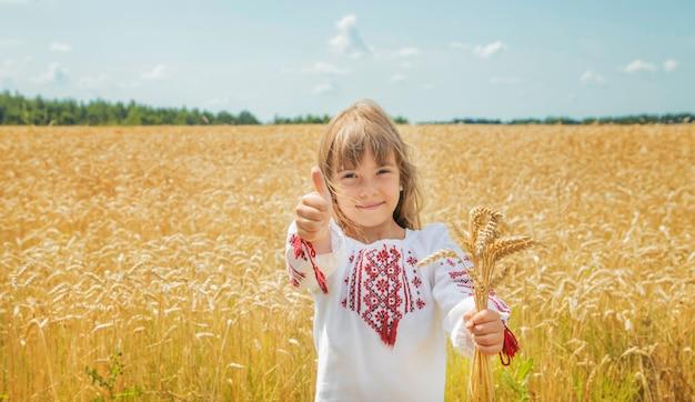 Ребенок на пшеничном поле в вышитой рубашке.