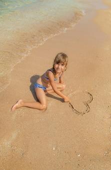 Ребенок рисует в песке на пляже
