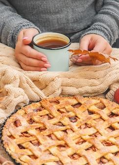 一杯のお茶とリンゴとシナモンのパイを持つ少女。