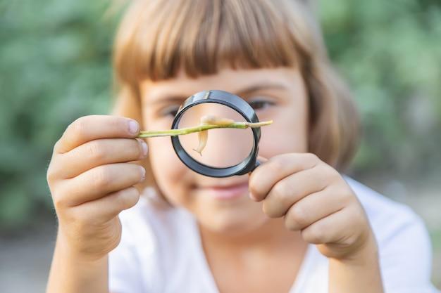 彼女の手に虫眼鏡を持つ子供。