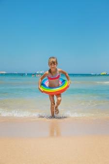 海で救命浮き輪を持つ子供