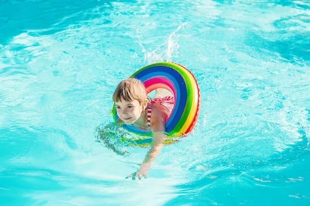 子供が命を守る人と一緒にプールで泳ぎます。セレクティブフォーカス