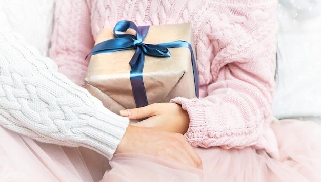 男と女の手の中の贈り物。セレクティブフォーカス。