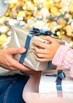 クリスマスは男性と女性の手にプレゼントされます。セレクティブフォーカス。