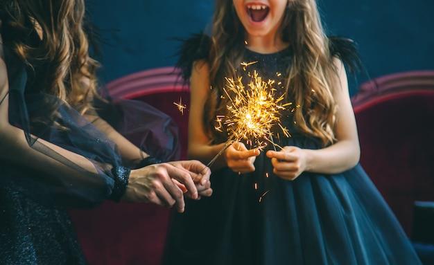 母と娘はクリスマスの夜に花火をつけました。