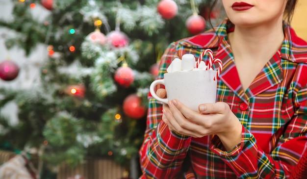 クリスマスの朝、マシュマロとココアのカップとパジャマの女性。セレクティブフォーカス。