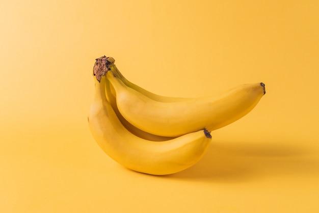 ミニマリズムスタイル。黄色の背景に黄色の熟したバナナ果実の果実パターン。