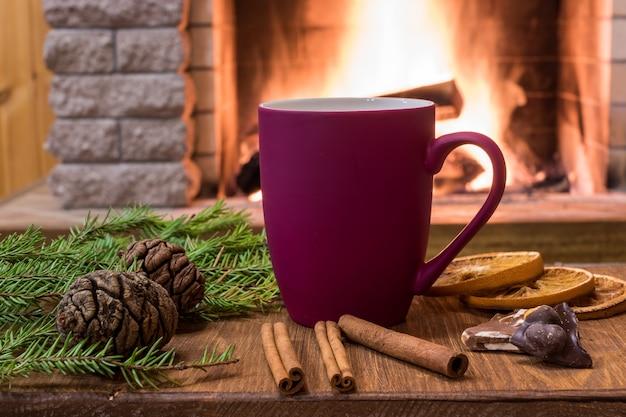 温かい飲み物のマグカップと暖炉のそばの居心地の良いシーン