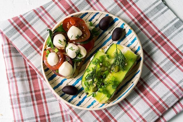 Бутерброды или тапас с хлебом, сливочным сыром и овощами.