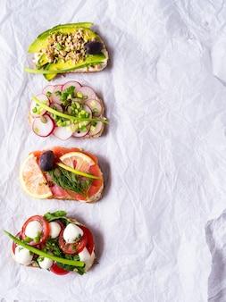 Бутерброды или тапас с хлебом, сливочным сыром, овощами.