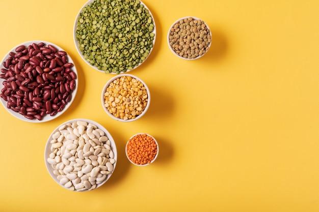 黄色の背景上のエンドウ豆、レンズ豆、豆、豆類の品揃えの平面図です。