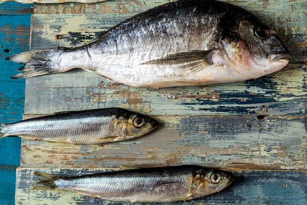 ニシンの魚とスズキの魚、古い青い木製の背景、フラットレイアウト、コピースペース。