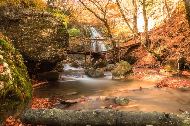 美しい滝と前景の小さな橋のある風景。