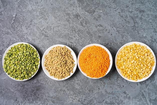 灰色の背景上のエンドウ豆、レンズ豆、豆類の品揃えの平面図です。