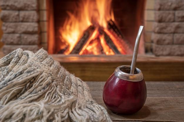 カントリーハウスの居心地の良い暖炉のそばの、仲間と飲み物とウールのスカーフのための伝統的なカップ。