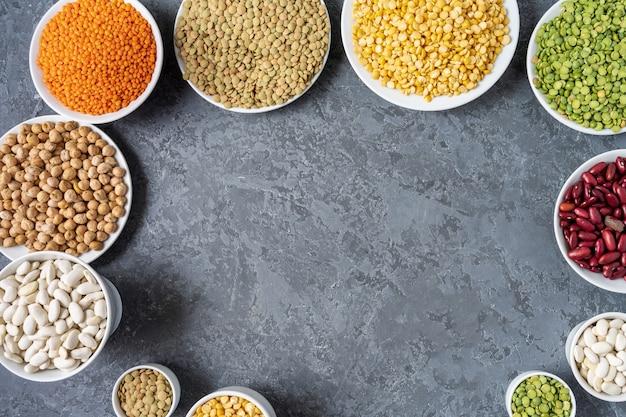 エンドウ豆、レンズ豆、豆、豆類の灰色の背景上の品揃えの平面図です。
